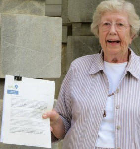 A woman holding up a binder-clipped packet of papers with the AAUW logo on the top.