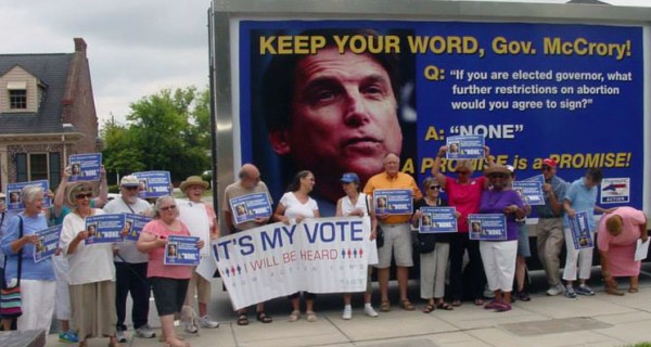 """A line of women holding posters in front of a truck with McCrory's face on it that reads """"Keep your word."""""""
