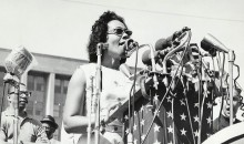 Coretta Scott King stands at a podium and delivers a speech.
