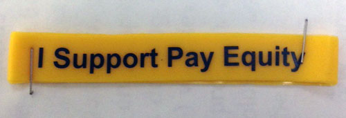 """Yellow bracelet that says """"I Support Pay Equity"""""""