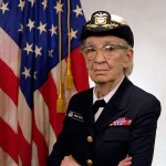 Grace Murray Hopper stands in Navy uniform in front of an American flag.