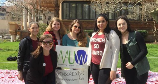 Students at University of Pittsburg stand with AAUW banner in front of their sexual assault awareness project, featuring red cups, to draw attention to victims of sexual assault.