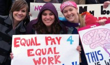 """A group of eight young stand with posters, one reading """"Equal Pay 4 Equal Work I am not worth LESS."""""""