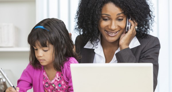 A woman talking on the phone and looking at her laptop with a daughter in her lap.