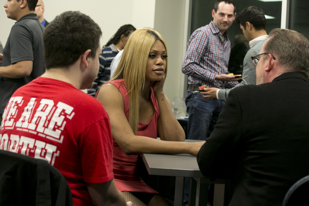 Laverne Cox sits at a table with a group of people.