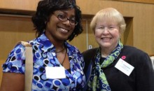 Two ladies in AAUW colors, one in a bright blue shirt, and the other with a blue and green paisley scarf, smile for a photo.