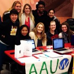 A group of young women gather around a table with an AAUW sign.