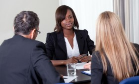 A young woman sits at a conference table with two people interviewing her.