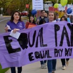 "A group of students marching and holding a banner reading, ""Equal Pay Now"""