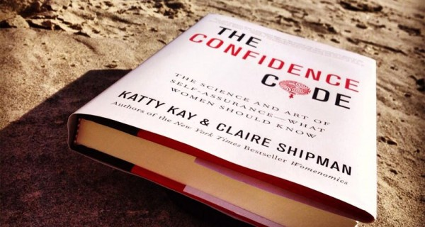 """A copy of the book """"The Confidence Code"""" lying in the sand."""