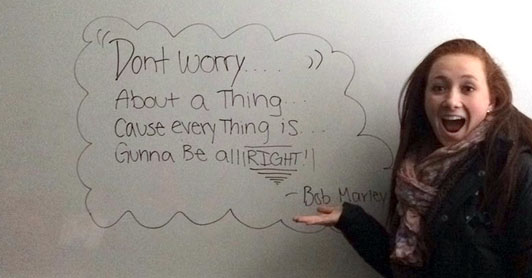 """Cathryn Garrett smiles and points to a sign that reads, """"Don't worry about a thing."""""""