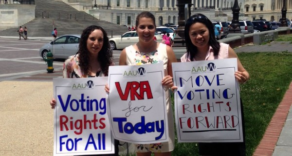 Three women AAUW staff hold signs and attend a voting rights rally at the United State Capitol.