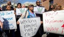 A group of women and men carrying signs supporting raising the minimum wage