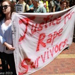 A young woman holds a banner in front of a crowd. The banner reads, Justice for Rape Survivors