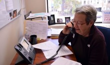 Patty sits at her desk and makes a phone call.