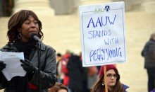 An African American woman stands at a microphone while people in the background hold signs during a rally at the U.S. Supreme Court in support of Peggy Young's discrimination case.