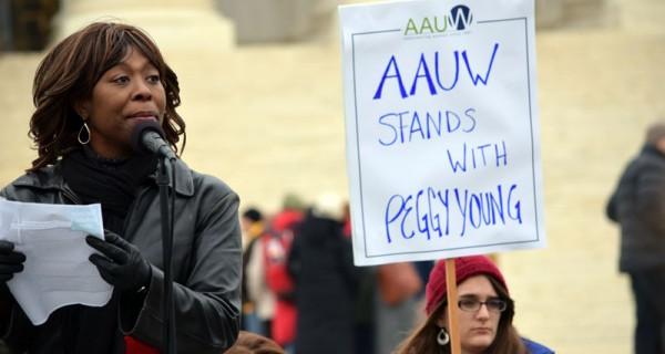 A woman stands at a microphone while people in the background hold signs.