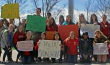 A group of about 20 college students with signs gather for a photo.