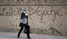 A Tunisian woman photographed just before the 2011 election walks by a wall with graffiti against secularism.