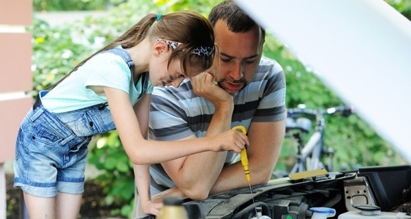 Girl in overalls learns how to check the oil in family car with her dad.