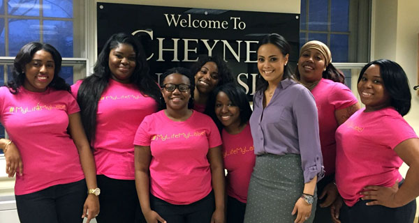 A group of women students in front of a Cheyney University banner