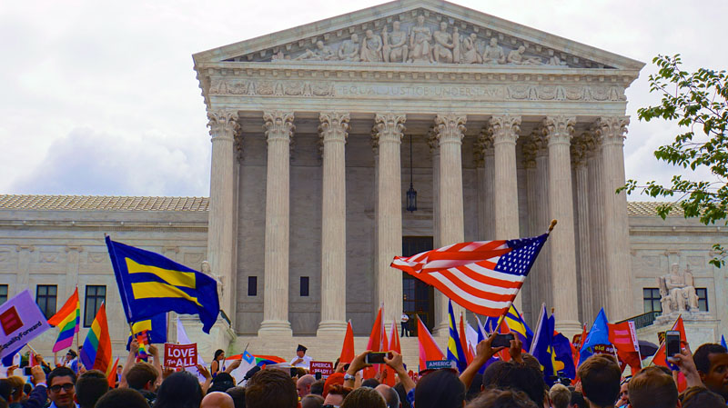 Happy crowds fly U.S. and LGBT flags outside the Supreme Court