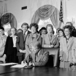 President Jimmy Carter signs a document in the White House with more than a dozen women and men standing behind him.