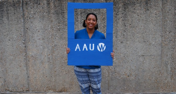 College student standing with AAUW sign around her head.