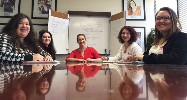 A group of women students working at a reflective table