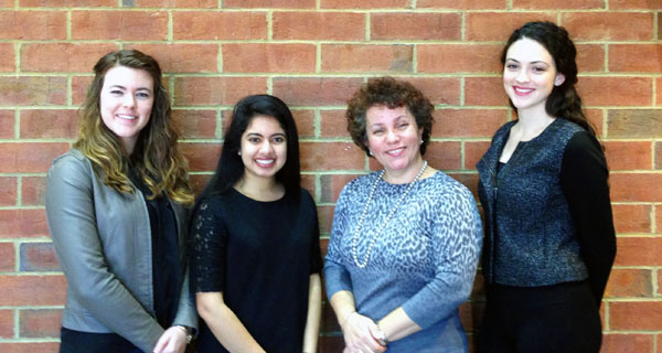 A group of women students standing together in front of a brick wall