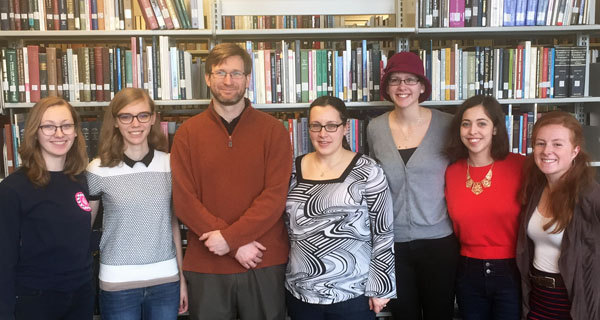 A CAP group of students with their adviser in the library