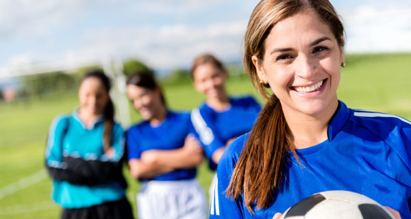 Happy football player with her team at the soccer field