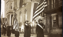 An old photo of women marching down the street with American flags