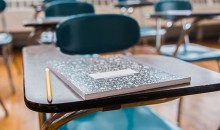 A notebook and pencil on a desk in an empty school classroom