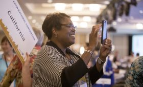 Woman using mobile phone at convention to contact her senator