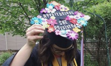 "A woman student wearing a graduation gown and cap with the words ""Nevertheless, she persisted"""