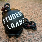 "Black ball and chain with the words ""Student Loans"" painted on them."