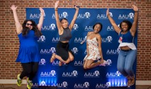 Four African American attendees at the 2017 National Conference for College Women Student leaders smile and leap in front of an AAUW bug banner.