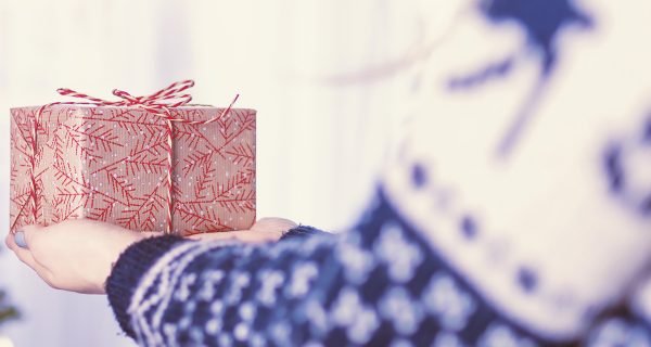 Woman wearing winter sweater handing holiday gift out to someone