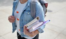 Woman college student in a jean jacket and black pants carrying a backpack, standing and hold an armload of books.