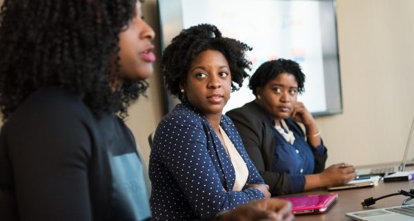 Three female African American tech professionals participate in a meeting discussion.