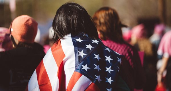 A woman at the 2018 Women's March in Phoenix, Arizona, wear an American flag over her back and shoulders. Photo taken from behind the woman.