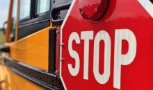 Close-up of red stop sign on a yellow school bus
