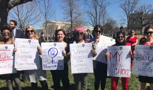 "Women holding protest signs on Capitol Hill, including ""Women's voices for women's choices"" and ""Be bold for change."""