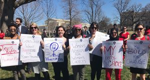 """Women holding protest signs on Capitol Hill, including """"Women's voices for women's choices"""" and """"Be bold for change."""""""