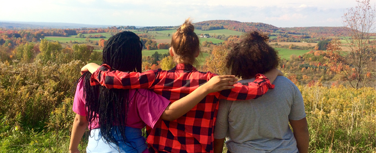 Diverse group of three woman hugging each other by the shoulders look out over the horizon. Photo shot from behind.