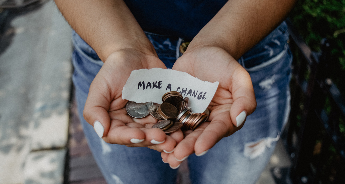 """Close up of woman's hands holding U.S. coins and small note that says, """"Make a change."""""""