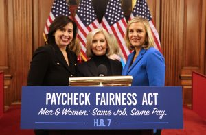 AAUW CEO Kim Churches, Senior VP of Public Policy and Research Deborah Vagins, and equal pay advocate Lilly Ledbetter smile behind a podium with a sign that reads 'Paycheck Fairness Act: Men and Women: Same Job, Same Pay. H.R. 7'