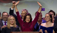 Michigan Governer Gretchen Whitman (Brunette on dark red dress) with her hands raised in celebration behind a podium.